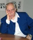 А. П. Сухарев сидит за столом