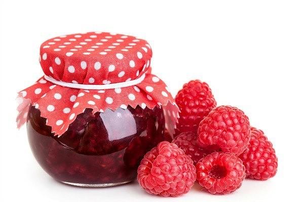 ягоды малины лежат у банки с вареньем