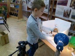 Участник студии устанавливает декорации для будущего мультфильма.