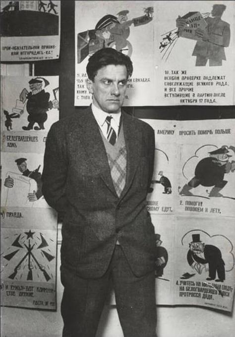 Фотография Владимира Маяковского в костюме, стоящего на фоне сатирических плакатов