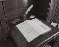 книга на столе и перо с чернильницей