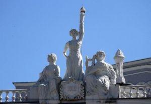 На фоне голубого неба скульптуры трех муз искусства.