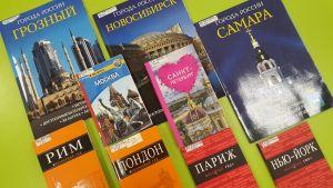 На зеленом столе разложены книги о городах: Москва, Санкт-Петербург, Грозный, Лондон, Париж, Нью-Йорк
