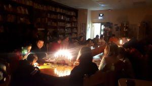люди сидят в темноте за столом