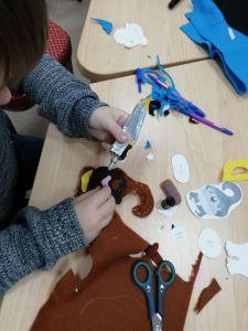 Участник студии создает мягкий брелок из фетра ввиде обеъянки