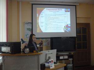 девушка лектор стоит перед большим экраном