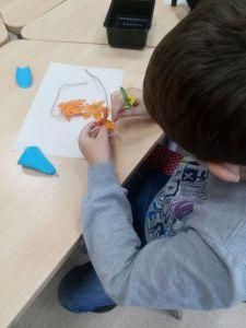 Участник студии создает брошь из фоамирана.