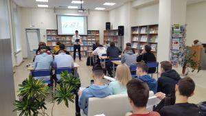 В просторной аудитории за столами сидят студенты, лектор читает лекцию.