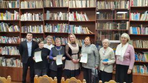 Группа слушателей курсов в подарками с сертификатами в руках на фоне книжных стеллажей.