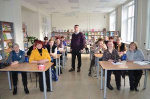 В учебной аудитории за столами сидят слушатели, лектор стоит в центре между столов.