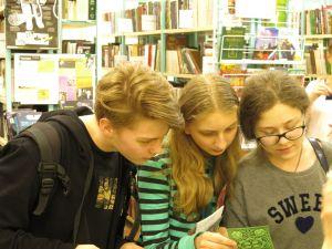 Молодые ребята читают книгу.