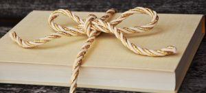 книга, перевязанная шнурком в виде бантика