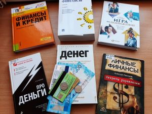 На столе лежат книги о финансах и деньги