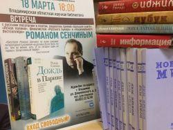 Книги Романа Сенчина на фоне афиши