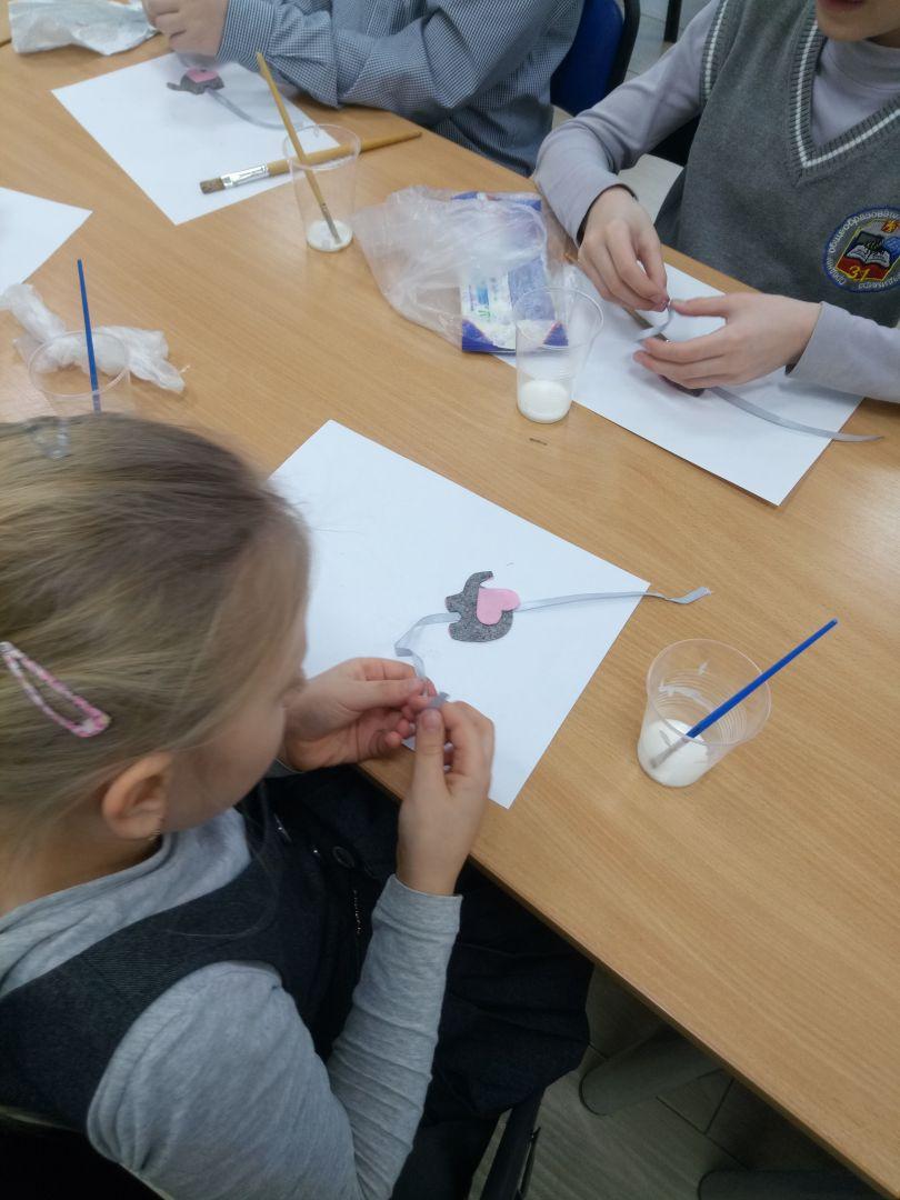 Юная участница творческого мастер-класса создает фетровую закладку ввиде слоника.