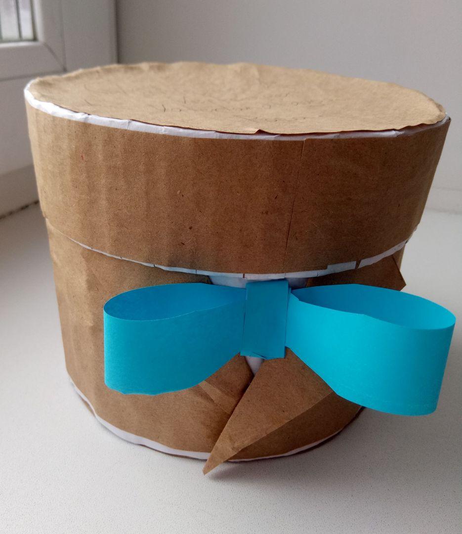 Круглая подарочная упаковка с голубым бантом.