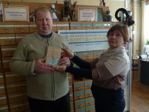 Сотрудники библиотеки дарят книгу первому посетителю