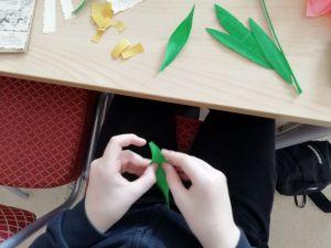 Участник студии создает из гофрированной бумаги яркие тюльпаны.