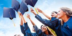 выпускники в мантиях подбрасывают вверх академические шапочки