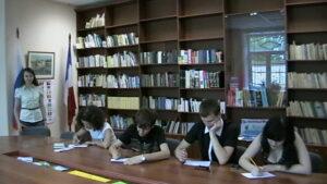 Преподаватель и студенты, пишущие за столом