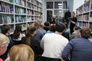 мероприятие в библиотеке. Книги на стеллажах, выступающий и публика