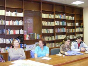 три женщины и молодой человек сидят за столом с наглядными материалами