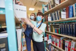 Библиотекари выбирают книги на полках